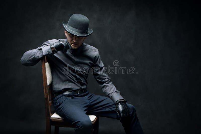 El criminal y el ladrón en guantes negros se están sentando en una silla fotografía de archivo libre de regalías