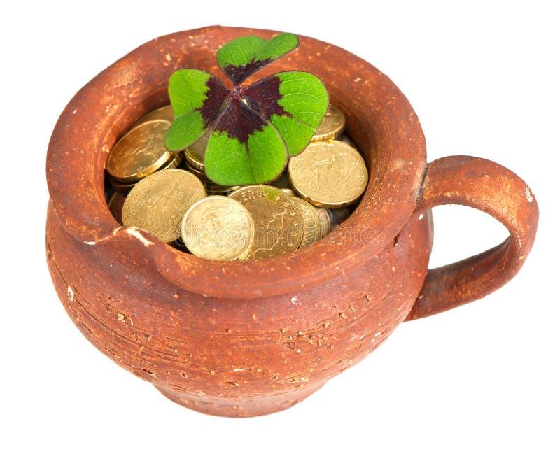 El crisol de cerámica viejo con las monedas del dinero y el trébol hojean foto de archivo libre de regalías