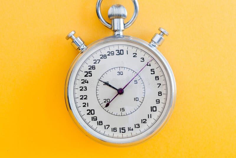 El cronómetro retro del cronómetro del estilo en el papel amarillo texturizó el fondo Concepto de la gestión de tiempo de la comp imagen de archivo