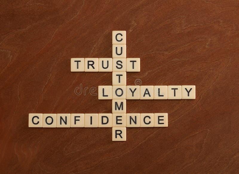 El crucigrama con palabras confía en, lealtad, confianza cliente fotografía de archivo