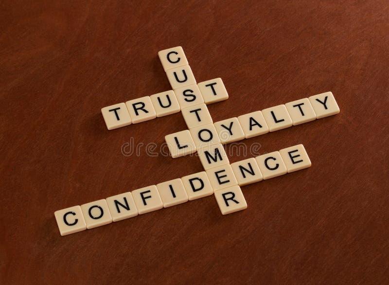 El crucigrama con palabras confía en, lealtad, confianza cliente imágenes de archivo libres de regalías