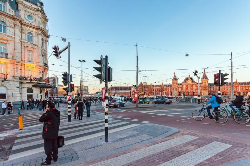 El cruzar en el Damrak holandés delante del stati central del tren fotos de archivo