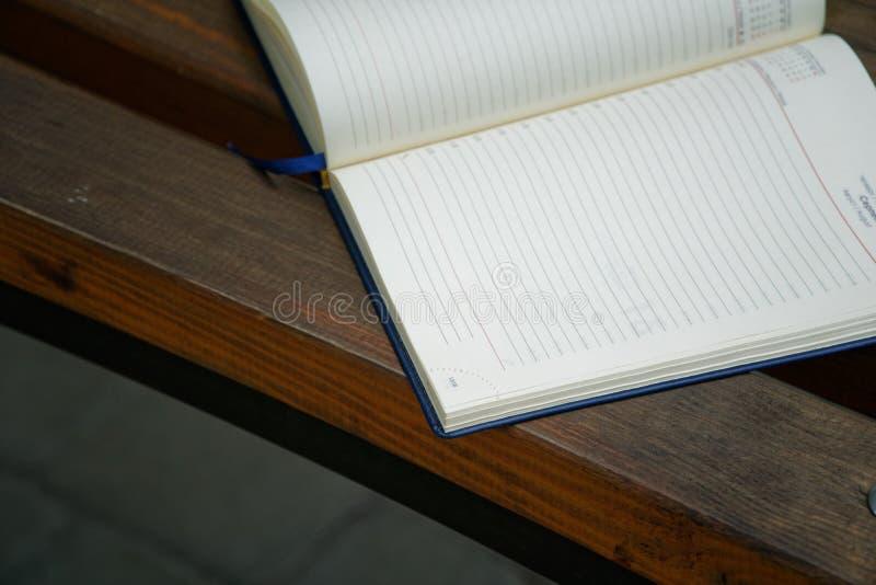 El cuaderno abierto miente banco en el parque, concepto del negocio fotos de archivo