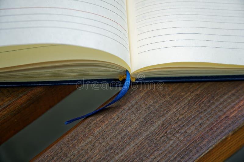 El cuaderno abierto miente banco en el parque, concepto del negocio foto de archivo libre de regalías