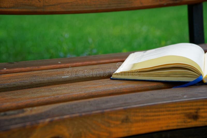 El cuaderno abierto miente banco en el parque, concepto del negocio fotos de archivo libres de regalías