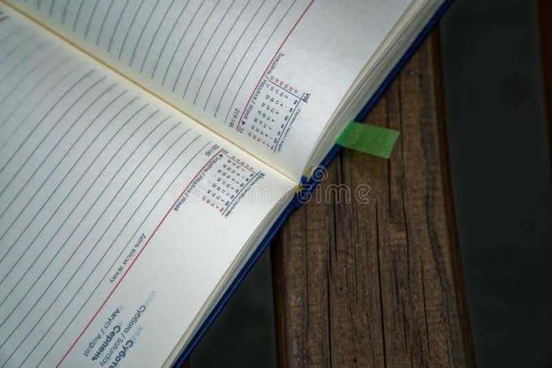 El cuaderno abierto miente banco en el parque, concepto del negocio foto de archivo