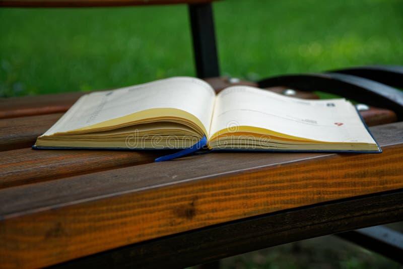 El cuaderno abierto miente banco en el parque, concepto del negocio fotografía de archivo libre de regalías