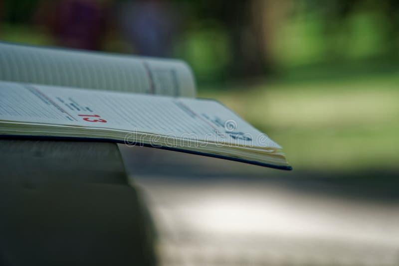 El cuaderno abierto miente en la barandilla de madera en el parque, concepto del negocio fotografía de archivo