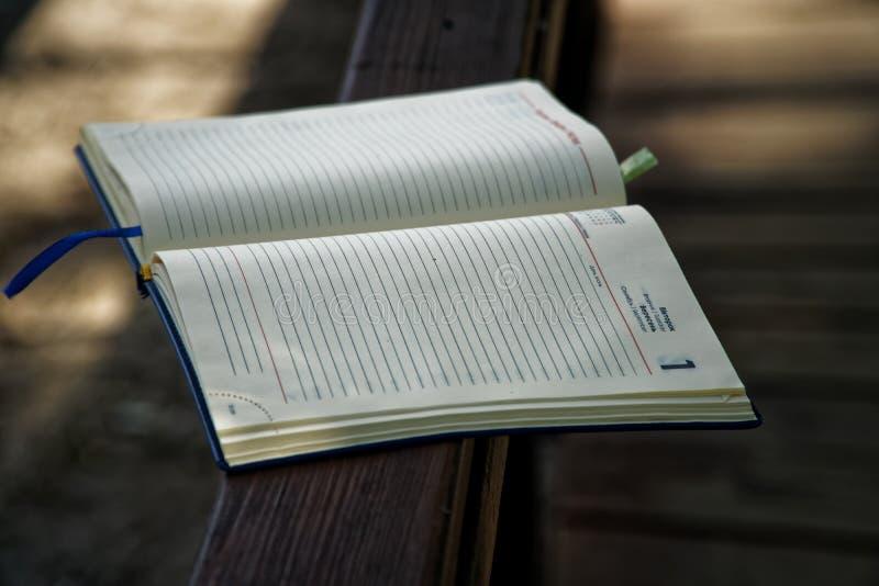 El cuaderno abierto miente en la barandilla de madera en el parque, concepto del negocio imagenes de archivo