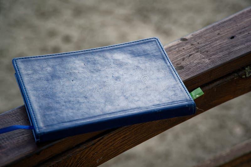 El cuaderno azul miente en la barandilla de madera en el parque, concepto del negocio imagen de archivo libre de regalías