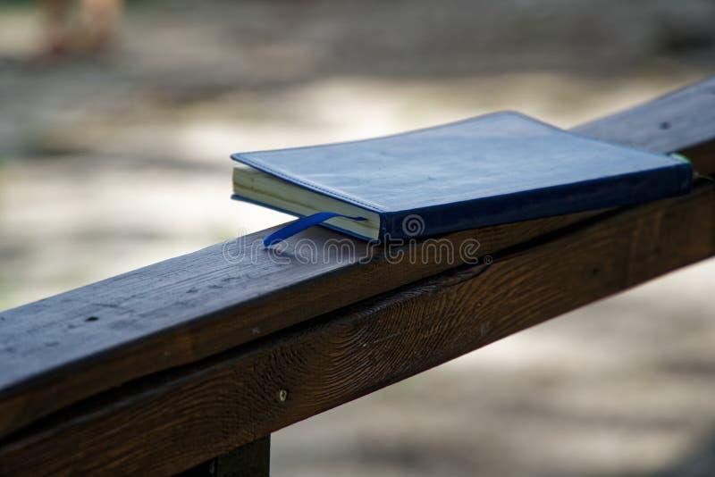 El cuaderno azul miente en la barandilla de madera en el parque, concepto del negocio fotos de archivo libres de regalías
