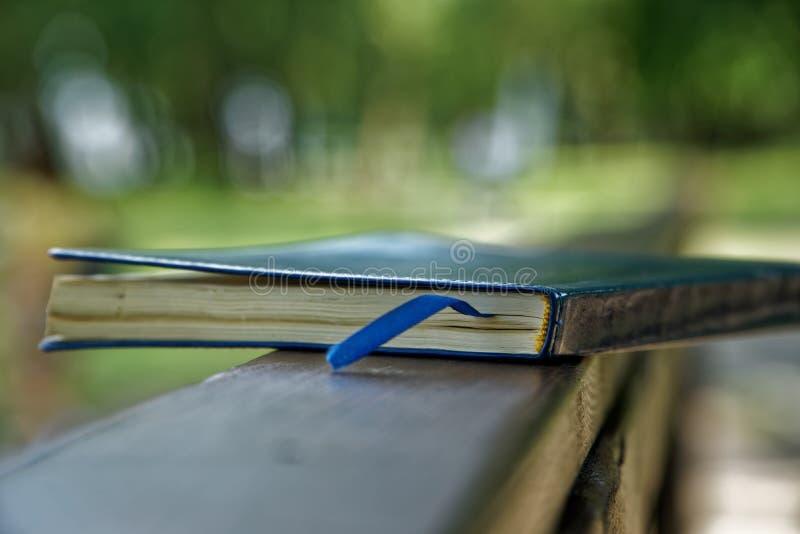El cuaderno azul miente en la barandilla de madera en el parque, concepto del negocio fotos de archivo