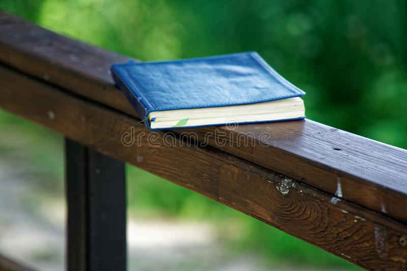 El cuaderno azul miente en la barandilla de madera en el parque, concepto del negocio imagenes de archivo
