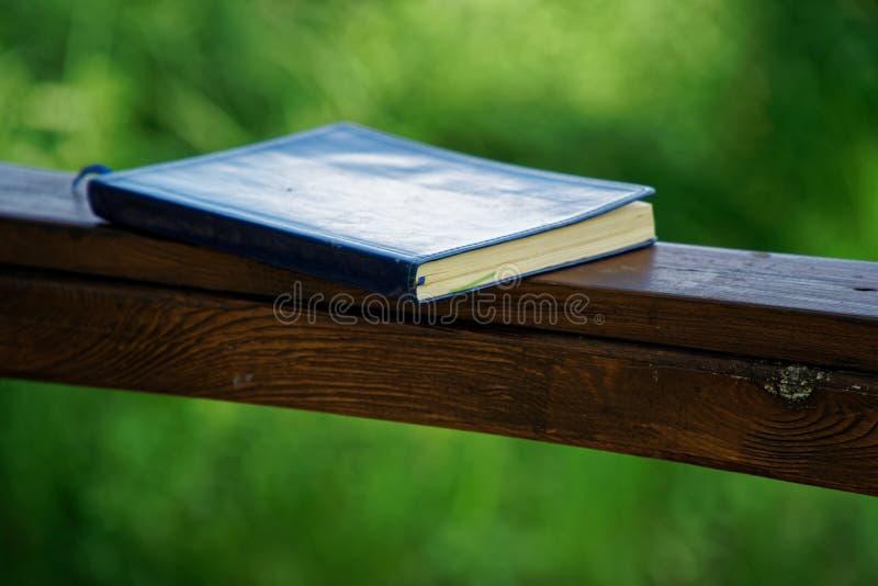 El cuaderno azul miente en la barandilla de madera en el parque, concepto del negocio fotografía de archivo