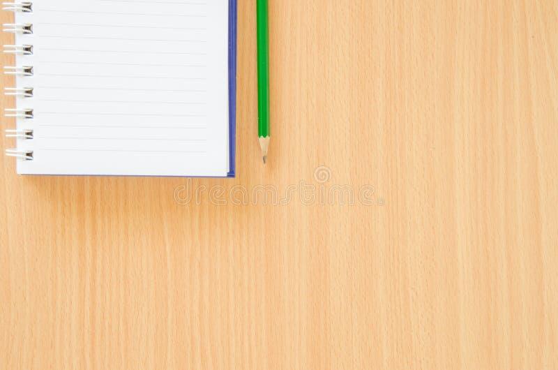 El cuaderno blanco y el lápiz verde en haya colorean el fondo con fotos de archivo