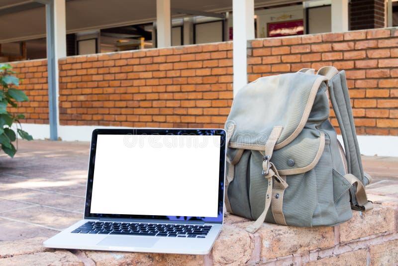 El cuaderno de la pantalla en blanco, el ordenador portátil y el viaje verde empaquetan en el parque Ver fotos de archivo