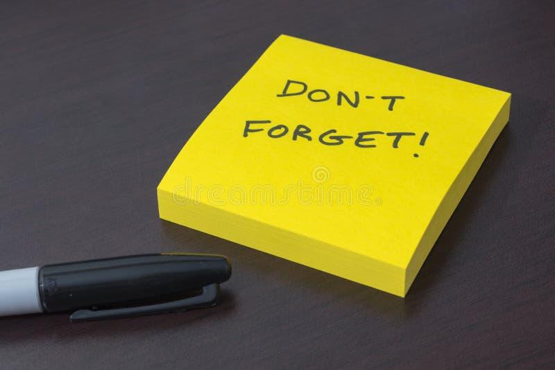 El cuaderno de notas pegajoso con el recordatorio pone el ` t olvida fotos de archivo libres de regalías