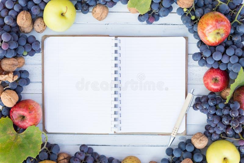 El cuaderno en blanco con el copyspace y el otoño da fruto marco imagen de archivo