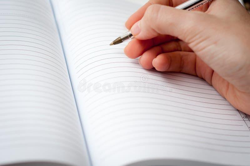 El cuaderno escribe foto de archivo libre de regalías
