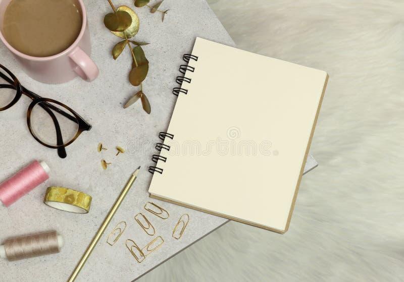El cuaderno, los accesorios de oro de la oficina, la taza de café, los hilos, los vidrios en la tabla del granito y el piso blanc imagen de archivo