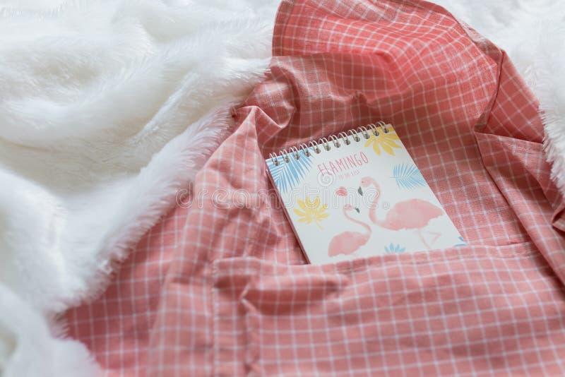 El cuaderno rosado del flamenco con para hacer la lista fijó en el paño rosado de la rejilla imagen de archivo libre de regalías