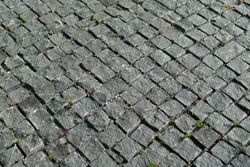 El cuadrado alineó con el guijarro o pavimento de la piedra, calzada o camino imagen de archivo