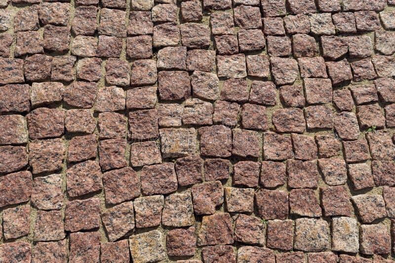 El cuadrado alineó con el guijarro o pavimento de la piedra, calzada o camino foto de archivo