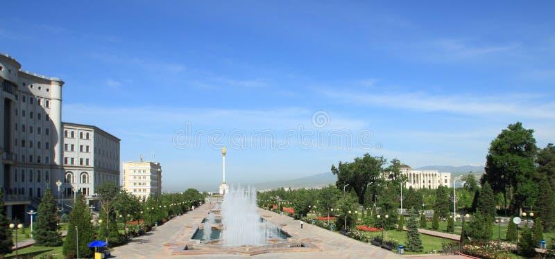 El cuadrado, el parque y el stele con el emblema Tayikistán en la ciudad de Dushanbe, Tayikistán fotos de archivo