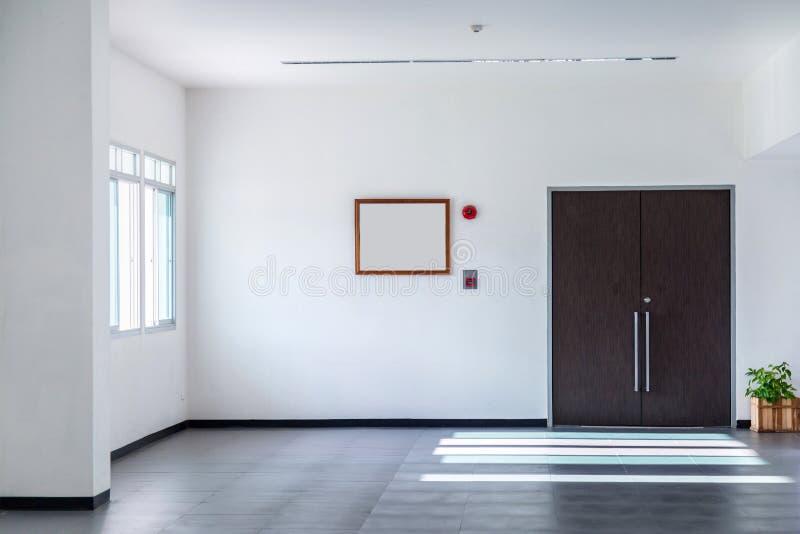 El cuarto blanco tiene puertas, alarma de incendio y árboles marrones en potes T fotografía de archivo