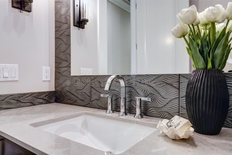 El cuarto de baño blanco y marrón se jacta un escondrijo llenado de vanidad de color topo imagen de archivo libre de regalías