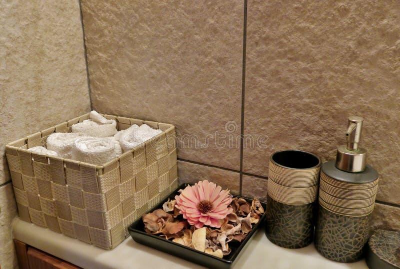 El cuarto de baño con las toallas, las flores y el cuidado bate imagenes de archivo