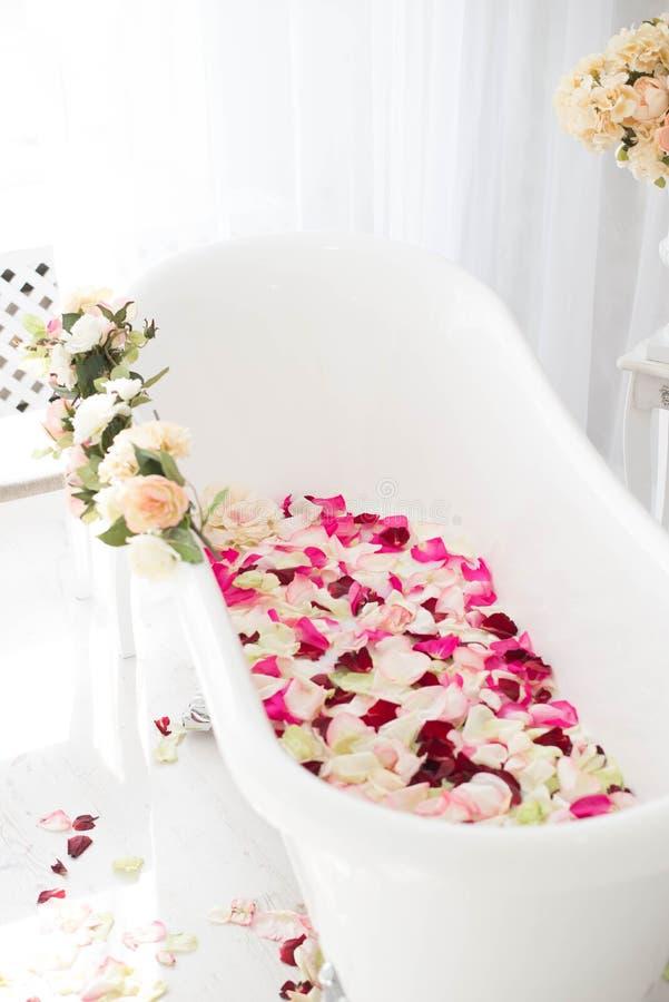 El cuarto de ba?o est? en un cuarto ligero adornado con las flores y los p?talos de rosas fotografía de archivo libre de regalías