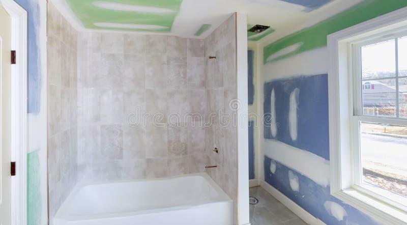 El cuarto de baño remodela progresa como la mampostería seca se alisa, cubriendo costuras y los tornillos con la cinta foto de archivo libre de regalías