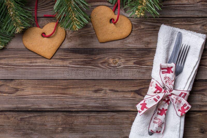 El cubierto de la tabla de la Navidad con la bifurcación y el cuchillo, la cinta adornada y el arco, pino de la Navidad ramifica  foto de archivo libre de regalías