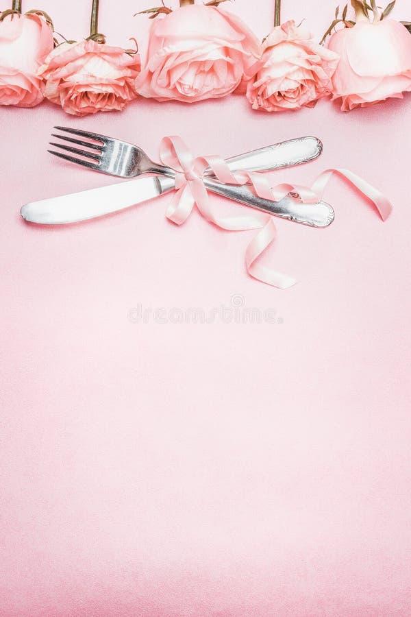 El cubierto romántico de la tabla con la cinta y las rosas confinan la decoración en el fondo pálido rosado, visión superior imagenes de archivo
