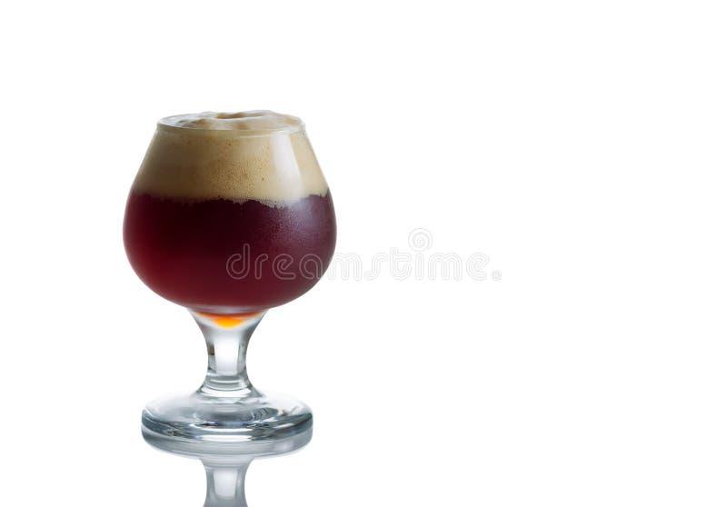 El cubilete de cristal llenó de la cerveza oscura fresca en blanco imagenes de archivo