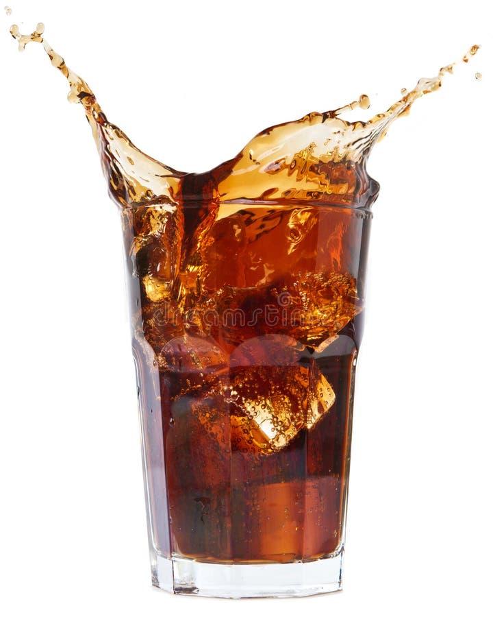 El cubo de hielo droped en vidrio y salpicar de la cola imagenes de archivo