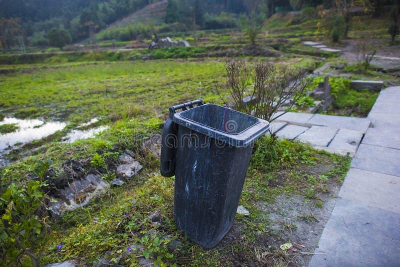 El cubo de la basura al borde del campo fotos de archivo