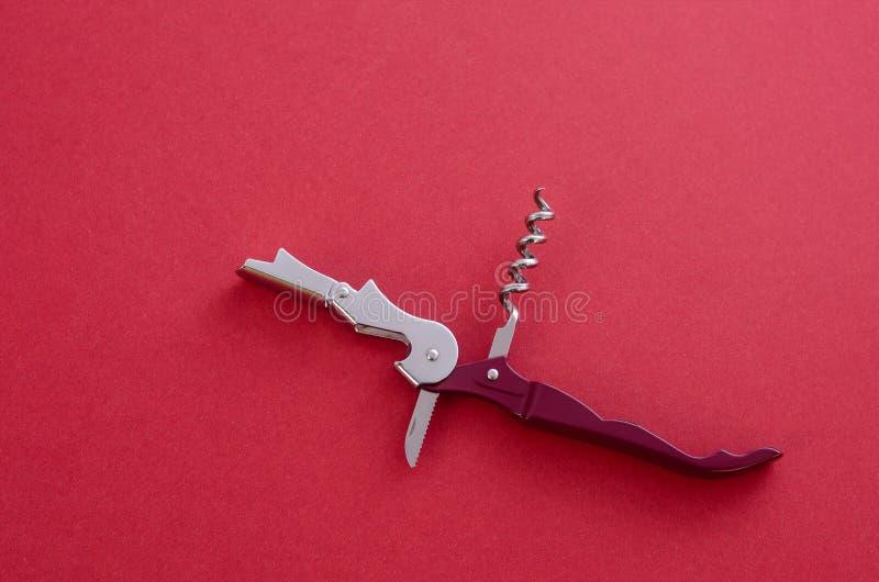 El cuchillo del sommelier abierto con el sacacorchos y el abrebotellas, profesional del cuchillo del camarero, en fondo rojo imagenes de archivo