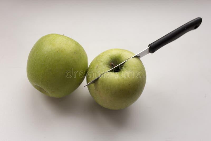 El cuchillo perforó la manzana Dos manzanas en un fondo blanco imagen de archivo