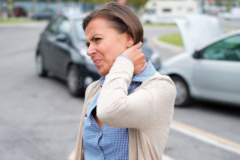 El cuello de la mujer dañó después de choque de coche en la calle imagenes de archivo
