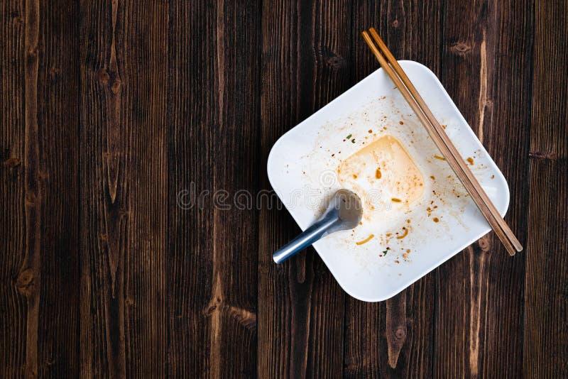 El cuenco blanco vacío de los tallarines con la cuchara y los palillos después de comen en w imágenes de archivo libres de regalías