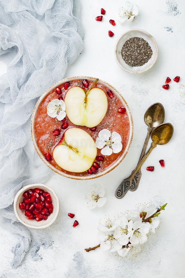 El cuenco con las semillas del chia, granada del smoothie de Superfoods, cortó manzanas y la miel Endecha de arriba, plana Comida imagen de archivo