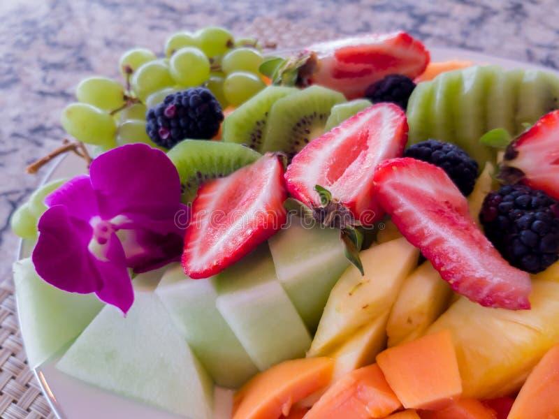 El cuenco de fruta con las fresas, el mango, la papaya, el melón, el kiwi y las uvas para el desayuno adornado con una púrpura de fotos de archivo libres de regalías