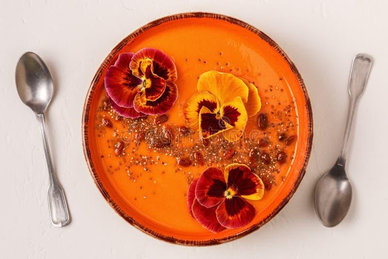 El cuenco del Smoothie con el pensamiento comestible florece, las semillas del chia, berrie del goji imágenes de archivo libres de regalías