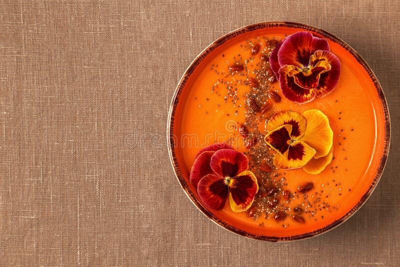 El cuenco del Smoothie con el pensamiento comestible florece, las semillas del chia, berrie del goji foto de archivo libre de regalías