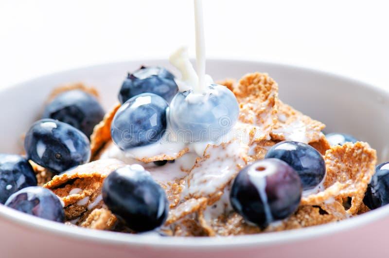 El cuenco lleno del muesli en una tabla blanca con el arándano y la leche salpican Cereales de desayuno sanos con la leche, semil imagen de archivo