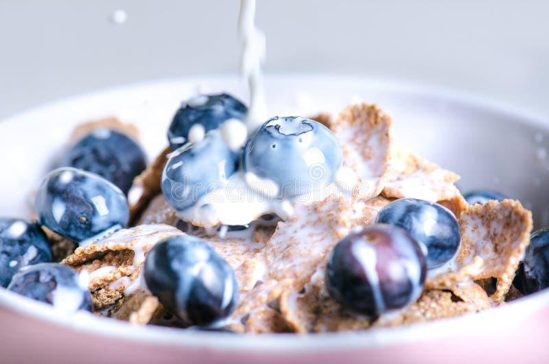 El cuenco lleno del muesli en una tabla blanca con el arándano y la leche salpican Cereales de desayuno sanos con la leche, semil fotos de archivo libres de regalías