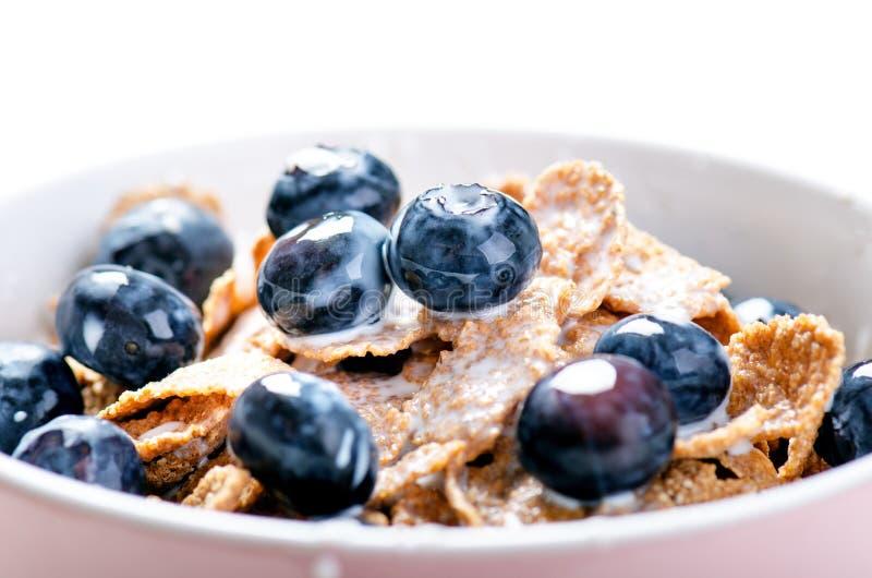 El cuenco lleno del muesli en una tabla blanca con el arándano y la leche salpican Cereales de desayuno sanos con la leche, semil fotos de archivo