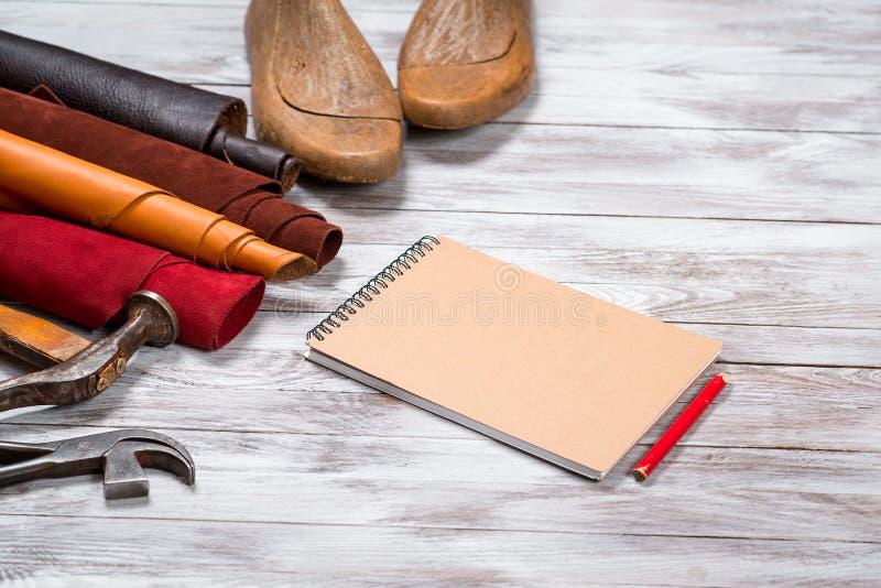 El cuero brillantemente coloreado en los rollos, herramientas de funcionamiento, zapato dura, cuaderno con el lápiz en el fondo b fotografía de archivo libre de regalías